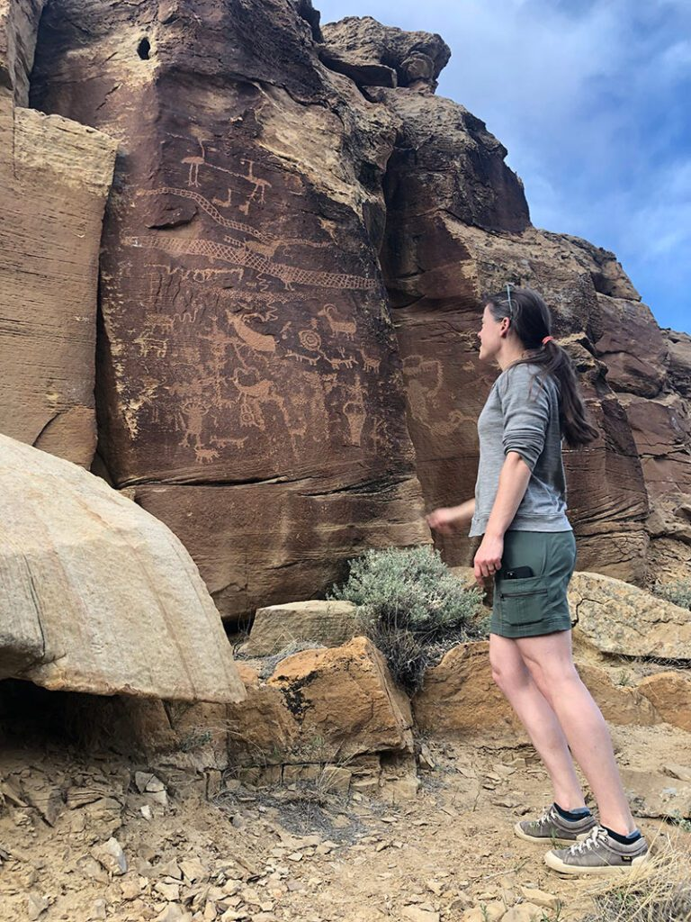 PaleoWest employee examining the amazing rock art on display at canyon site